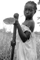 A young African girl wielding a metal hoe.